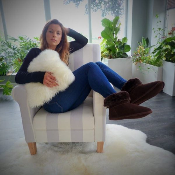 Chocolate Sheepskin Slipper boots worn by female sat on a stripe chair on an ivory sheepskin rug