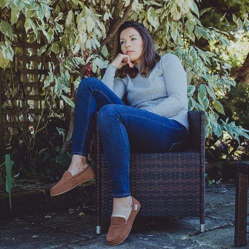 Ashley Unisex Sheepskin Slippers worn by female sitting in rattan chair outside