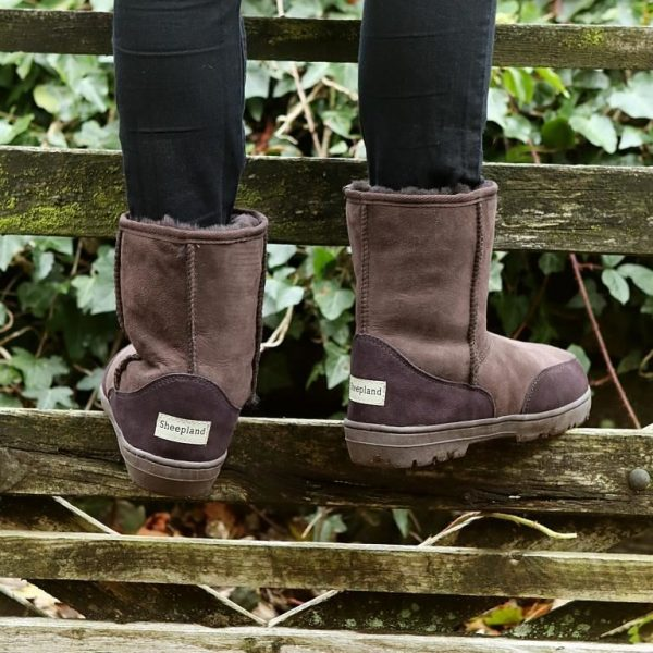 Sheepskin outdoor boots in brown, model standing on a gate