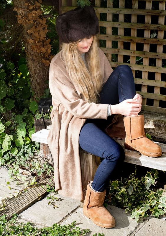Tan Sheepskin outdoor boots, female model sitting on wooden bench, wearing Cossack hat