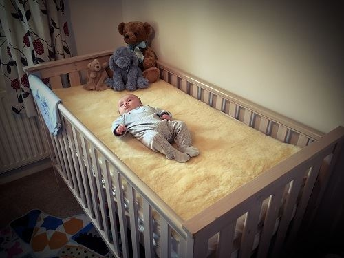 Baby lying on a Sheepskin in a Cot