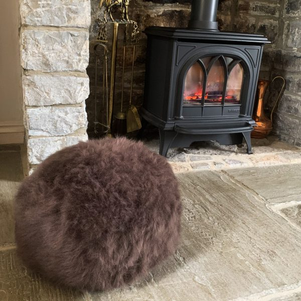 Brown sheepskin pouffe by log burner