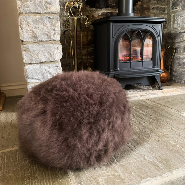 Brown Sheepskin Pouffe by fireplace
