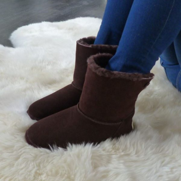 Chocolate sheepskin slipper boot, worn by model sat on an ivory sheepskin rug
