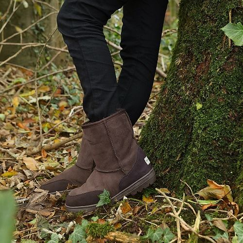 Brown slim fit sheepskin boots, female model standing against a tree, autumn day