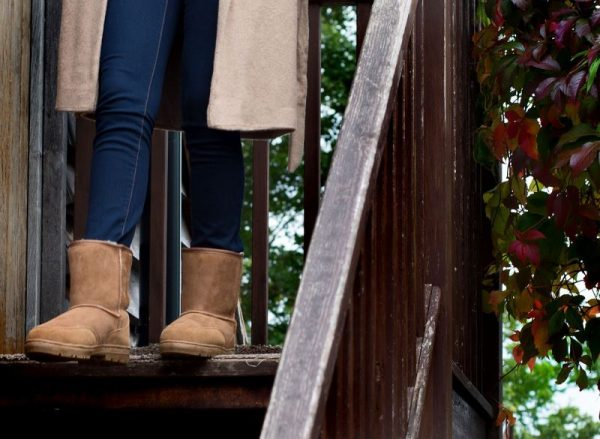 Tan slim fit sheepskin boots, female model walking down wooden steps