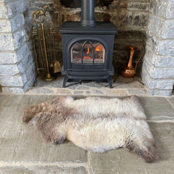 Rare Breed Undyed British Sheepskin Rug M71 in front of log burner