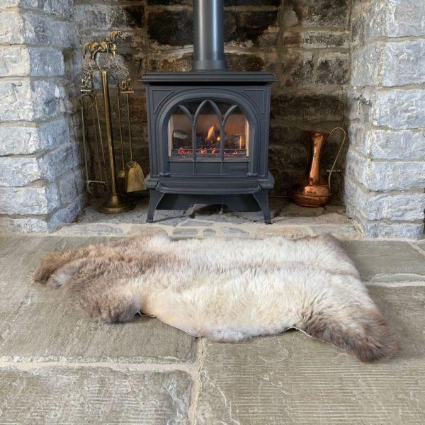 Sheepland Undyed British Sheepskin Rug M71 in front of log burner