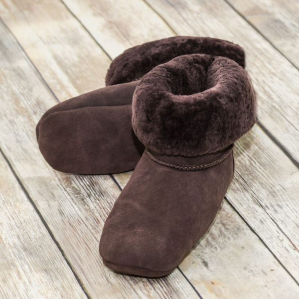 British made mocha house boots on a wooden background, fur collar