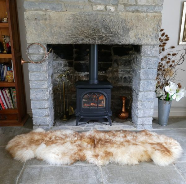 Sheepland Sheepskin Wolf Tipped Rug by Fireplace