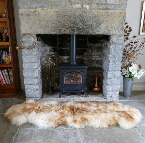 Sheepland Sheepskin Wolf Tipped Rug by Fireplace