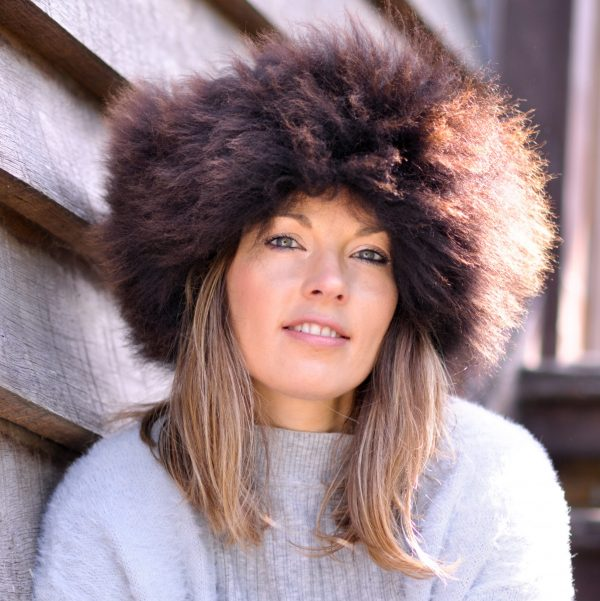 British sheepskin headband, women modelling the brown headband, face on with a wooden effect background