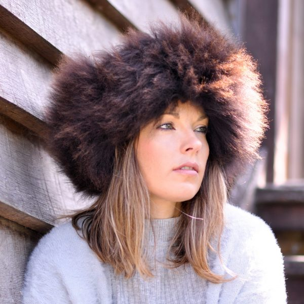 British sheepskin headband, women modelling the side view of the brown headband with a wooden effect background