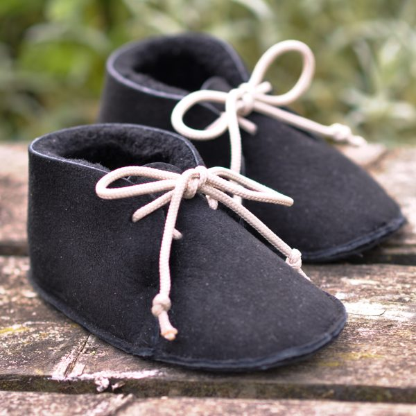 Sheepskin baby shoes with a wooden background
